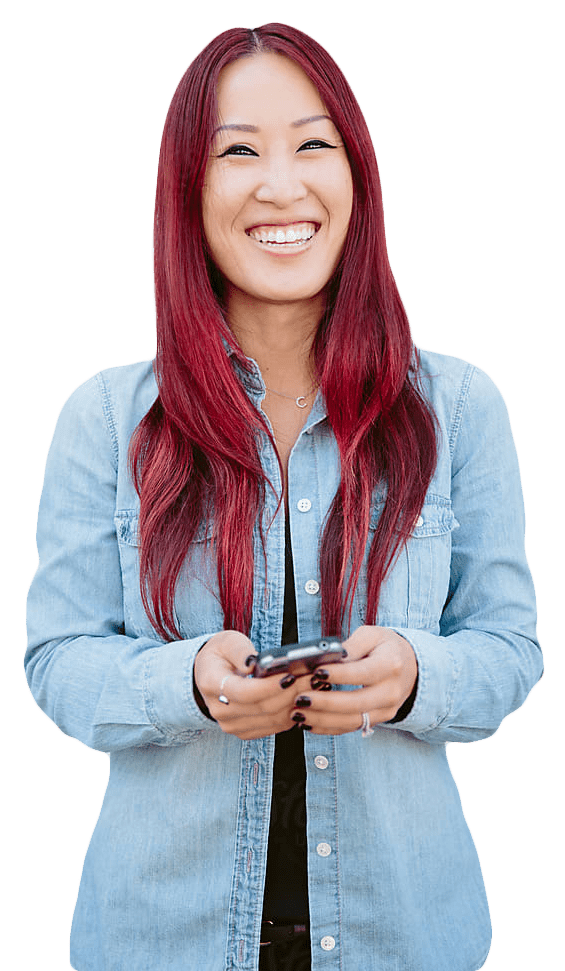 Woman with red hair smiling straight at the camera while holding a cell phone.