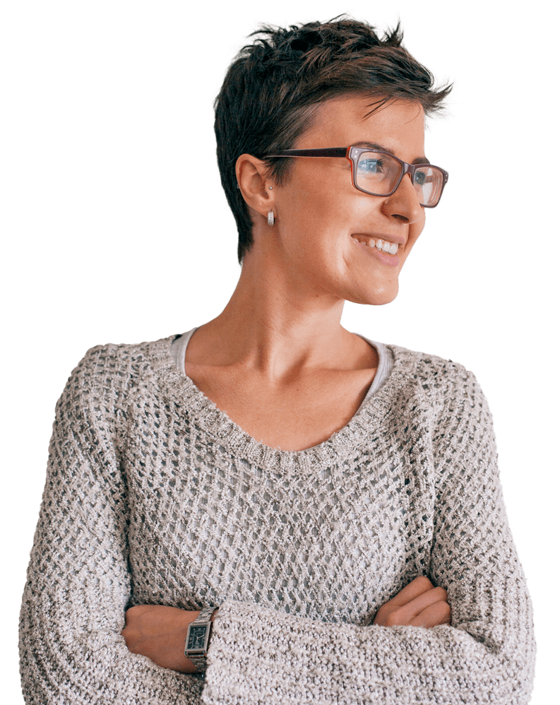 Woman in glasses smiling to the side with her arms crossed.
